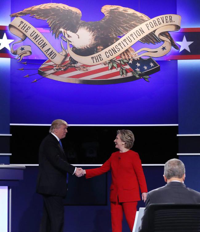 2 - El candidato republicano a la presidencia de Estados Unidos Donald Trump (i) y su rival demócrata Hillary Clinton (c) se dan la mano tras su primer debate hoy, lunes 26 de septiembre de 2016, en la Universidad Hosfra de Hempstead, Nueva York (EUA). Foto: EFE/Justin Lane